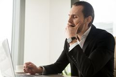 Tired sleepy businessman yawning in front of laptop at workplace royalty free stock image