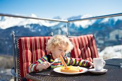 Child eating apres ski lunch. Winter snow fun for kids. Stock Photo