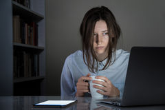 Tired sleepy female person with cup of coffee working at computer. Exhausted female person holds tea and looks at laptop pc screen at white desk in dark room royalty free stock images