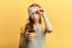 Tired sleepy girl has sad expression, holds disposable cup of drink royalty free stock images
