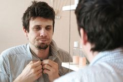 Free Tired Sleepy Man Who Has Just Woken Up Looks At His Reflection In The Mirror And Sees His Scruffy Appearance, Buttoning Royalty Free Stock Photo - 123798865