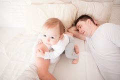 Tired and sleepy parents. In the bed with her todler baby in the morning Royalty Free Stock Image