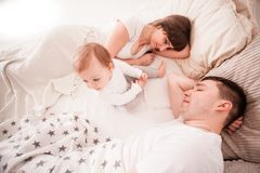 Tired and sleepy parents. In the bed with her todler baby in the morning Stock Photography