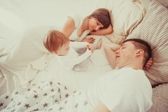 Tired and sleepy parents. In the bed with her todler baby in the morning Stock Photos