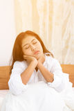 Tired sleepy woman waking up. While sitting in bed isolated on white background Stock Photography