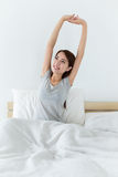 Tired sleepy woman waking up and yawning with a stretch while si Royalty Free Stock Images