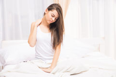 Tired sleepy woman waking up and yawning with a stretch while sitting in bed Stock Photography
