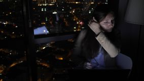 Tired sleepy woman is working on her computer at night near the window with cityscape. Tired sleepy woman is working on her computer at night near the window stock video footage