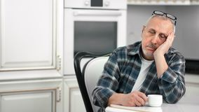 Tired sluggish aging male dozing during drinking tea at white kitchen medium shot