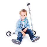 Tired small boy resting on scooter Royalty Free Stock Photo