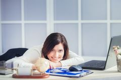 Tired woman at office desk in the evening Royalty Free Stock Photos