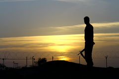 The tired soldier. A silhouette of a soldier in desert camp looking at sunset Royalty Free Stock Photography