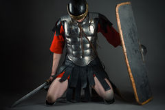 Tired soldier kneeling with a shield and a sword in hands. Isolated on gray background stock photos