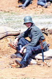 A tired soldier-reenactor sits on the ground. Stock Image