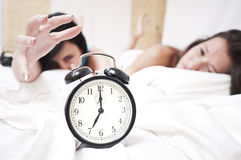 Tired spleepy women stopping a ringing clock. Tired sleepy women in the morning on white steets stopping a ringing clock looking like they don't want to wake up royalty free stock photos