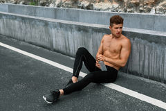 Tired Sports Man Resting After Running And Workout Exercising Outdoors. Sports. Tired Exhausted Athletic Man With Fit Muscular Body In Sportswear Resting After royalty free stock images