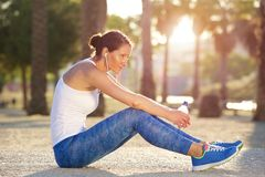 Tired sports woman sitting outside Stock Photo