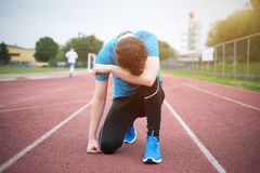 Tired sportsman feeling exhausted and defeated. On the track Stock Photography