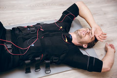 Tired sportsman lying on floor after training with ems Royalty Free Stock Image