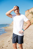 Tired sportsman standing and relaxing on the beach Stock Photo