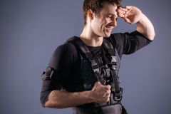 Sportsman wipes sweat after training with ems. Tired sportsman wipes sweat after training with ems Stock Photo