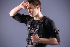 Sportsman wipes sweat after training with ems. Tired sportsman wipes sweat after training with ems Royalty Free Stock Image