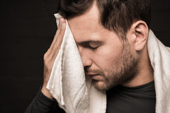 Tired sportsman wiping face by towel at gym locker room. On black background Royalty Free Stock Photos
