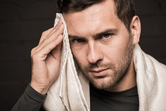 Tired sportsman wiping face by towel at gym locker room. On black background Stock Photos