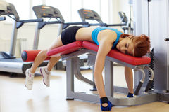 Tired sportswoman lying on sports bench Stock Photos