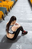 Tired sportswoman sitting on stadium stairs and resting. Running woman tired concept Royalty Free Stock Photo
