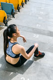 Tired sportswoman sitting on stadium stairs and resting. Running woman tired concept Stock Photos