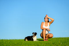 Tired sporty athlete taking a training break with her dog. Tired sporty woman taking a  running and exercising rest with her dog. Female athlete sweating after Royalty Free Stock Photo