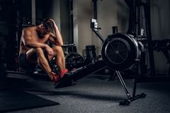 Tired sporty male after workouts on power exercise machine. Full body portrait of tired sporty male after workouts on power exercise machine in a gym club Royalty Free Stock Images