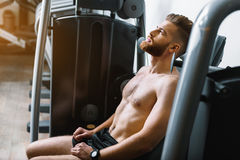 Tired sporty man in gymnasium Stock Image