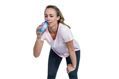 Tired sporty woman bending and drinking water Royalty Free Stock Images