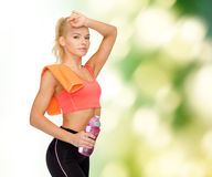 Tired sporty woman with towel and water bottle Stock Photo