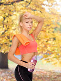 Tired sporty woman with towel and water bottle Royalty Free Stock Photography