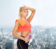 Tired sporty woman with towel and water bottle Stock Images