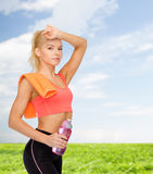 Tired sporty woman with towel and water bottle Royalty Free Stock Photos