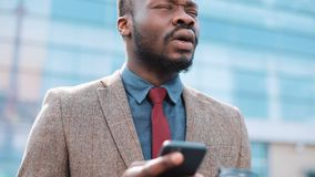 Tired and stressed African American businessman reads something in his smartphone standing outside. Man sms texting stock video