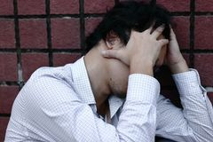 Tired and stressed Asian business man feeling exhausted. Stock Photos