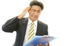 Tired and stressed Asian businessman Royalty Free Stock Photo