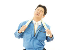 Tired and stressed Asian worker. An asian worker on white back ground Royalty Free Stock Image