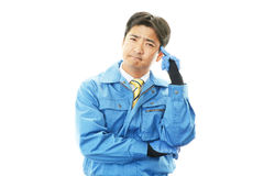 Tired and stressed Asian worker. An asian worker on white back ground Royalty Free Stock Photo