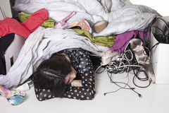 Tired and stressed girl sleeping under mess Stock Photo