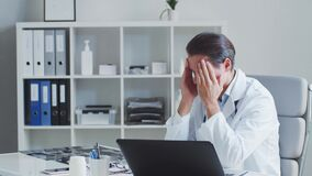 Tired and stressed medical doctor working in hospital office