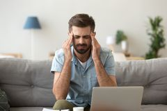 Tired stressed young man suffering from headache after computer work royalty free stock photos