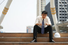 Tired or stressful businessman sit on the stairs after working. On the building background Royalty Free Stock Photos