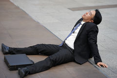 Tired or stressful businessman sitting on floor after being fired. Tired or stressful businessman sitting alone on the floor after being fired Royalty Free Stock Photography