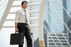 Tired or stressful businessman stand alone in city after working. Tired or stressful businessman stand alone in the city after working with a building background Stock Photos